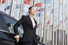 Businesswomen standing near car with flagpoles in background. Royalty Free Stock Photography
