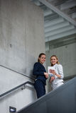 Businesswomen standing on staircase and using digital tablet royalty free stock photo