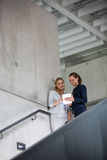 Businesswomen standing on staircase and using digital tablet royalty free stock image