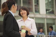 Businesswomen talking and drinking coffee outdoors Royalty Free Stock Photo