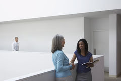 Businesswomen Talking In Office Hallway Stock Photo