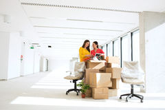 Businesswomen unpacking cardboard boxes in new office Stock Photos