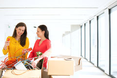 Businesswomen untangling cords while standing by cardboard boxes in new office Stock Image