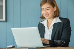 Businesswomen use laptop to find information on working with vintage blue backdrops in coffee shop royalty free stock image