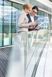 Businesswomen using digital tablet by glass railing Royalty Free Stock Image