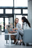 Businesswomen using laptop and having a discussion Stock Image