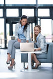 Businesswomen using laptop and having a discussion stock images