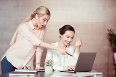 Businesswomen using laptop and pointing with pen at screen Royalty Free Stock Photography