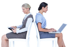 Businesswomen using laptop and reading book Stock Photo