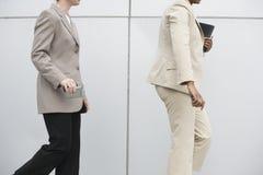 Businesswomen walking with cellphones. Midsection of two women walking with mobile phones Royalty Free Stock Photo