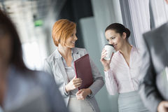 Businesswomen walking in office corridor Stock Photos
