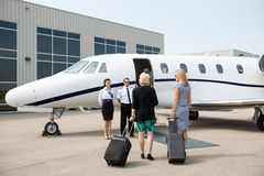 Businesswomen Walking Towards Private Jet. Rear view of businesswomen with luggage walking towards private jet while pilot and airhostess standing by Royalty Free Stock Photos
