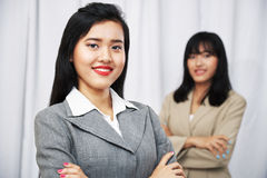 Businesswomen wearing suits standing and folding arms Royalty Free Stock Photos