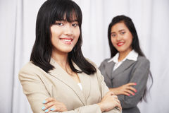 Businesswomen wearing suits standing and folding arms Royalty Free Stock Images