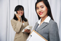 Businesswomen wearing suits standing and folding arms Stock Images