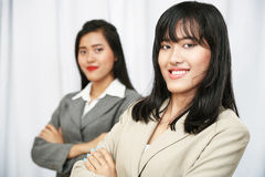 Businesswomen wearing suits standing and folding arms Stock Photography