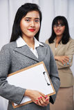 Businesswomen wearing suits standing and folding arms Stock Photos