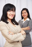 Businesswomen wearing suits standing and folding arms Royalty Free Stock Photo