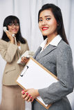 Businesswomen wearing suits standing and folding arms Stock Photo