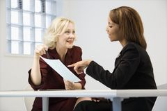 Businesswomen at work. Businesswomen sitting at office desk going over paperwork pointing and smiling stock photography