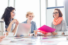 Businesswomen working at desk in creative office Stock Photography