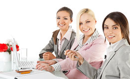 Businesswomen working desk laptop. Group of three happy businesswomen working behind desk with laptop, looking at camera Stock Images