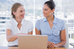 Businesswomen working with laptop. At desk in office Royalty Free Stock Image