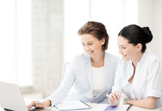 Businesswomen working with laptop in office Stock Images