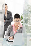 Businesswomen working in office. Young businesswoman working at desk in modern office, another talking on mobile phone in background Royalty Free Stock Images