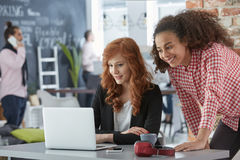 Businesswomen working on a project. Young smiling businesswomen working on a project in modern coworking office royalty free stock photography