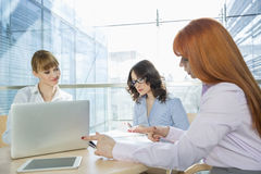 Businesswomen working at table in office Stock Images
