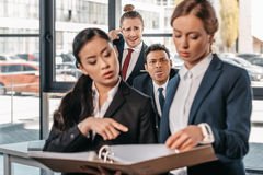 Businesswomen working together while businessmen grimacing behind, business team working concept Stock Image