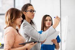 Businesswomen writing something to office board Royalty Free Stock Photography