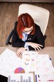 Businesswomna do ruivo que olha diagramas e cartas fotos de stock royalty free