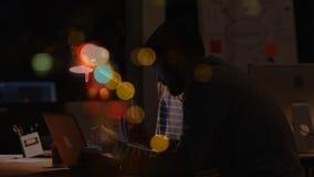 Businessworkers woking sobre el ordenador portátil el noche en la oficina con la animación colorida de la burbuja almacen de metraje de vídeo