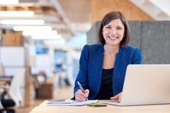 Busineswoman усмехаясь обширно пока работающ в ее кабине офиса Стоковая Фотография
