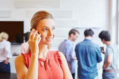Busineswoman calling with smartphone. In a start-up company Stock Photography
