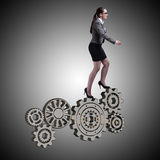 The busineswoman with cogwheels gear in teamwork concept. Busineswoman with cogwheels gear in teamwork concept Stock Photos
