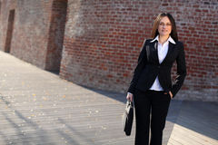 A busineswoman in front of a brick wall. A businesswoman is standing in front of a brick building Royalty Free Stock Image