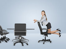 Busineswoman kneeling on chair and looking at Stock Photography