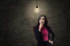 Busineswoman que piensa debajo de bombilla Foto de archivo