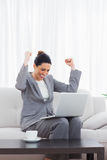 Busineswoman sitting on sofa using laptop cheering Stock Photo