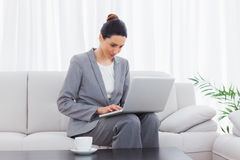 Busineswoman sitting on sofa using laptop Stock Photo