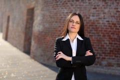 Busineswoman sta levandosi in piedi davanti ad un muro di mattoni immagine stock