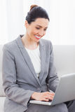 Busineswoman using laptop sitting on sofa Stock Photography