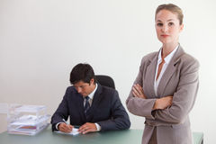 Busineswosman posing while her colleague is working Stock Images