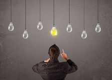 Businness guy in front of idea light bulbs concept. Businness guy in front of bright idea light bulbs concept Royalty Free Stock Photography