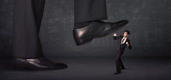 跨步在一个微小的businnessman概念的巨大的腿 库存图片