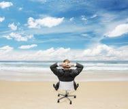 Businnessman che si siede sulla spiaggia Fotografia Stock