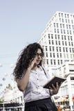 Businnesvrouw die op de mobiele telefoon met cliënt en controles het programma in haar notitieboekje spreekt royalty-vrije stock foto